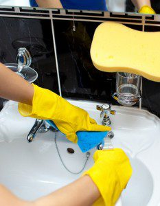 Close-up of a woman cleaning a bathroom's sink with a sponge and detergent spray
